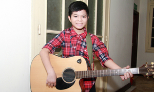 Quang Anh ôm guitar ra dáng nghệ sĩ