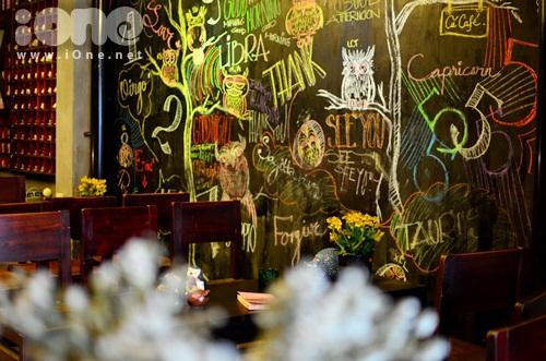H3 Không thể không ấn tượng với mảng tường đầy sắc màu bởi những nét vẽ đầy sáng tạo. Chỉ với những cây phấn màu dùng để viết bảng trên lớp học thường ngày, chủ nhân của quán đã hô biến mảng tường thô thành một bức tranh Cú mê hoặc.