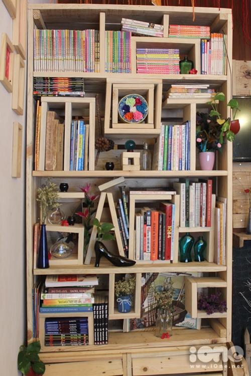 Một kệ sách lớn được bố trí ở cuối quán do chính tay cô chủ quán thiết kế và tự đóng lấy.