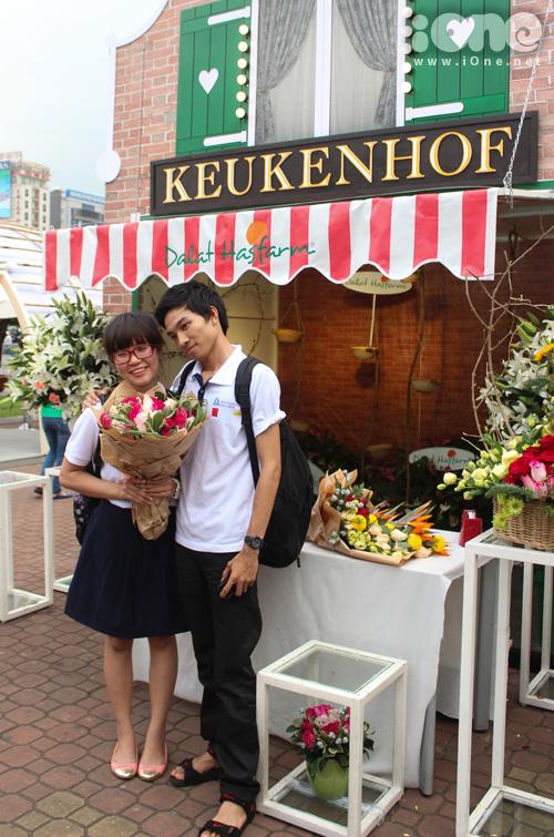 1 cặp đôi tranh thủ chụp ảnh trước quầy hoa.