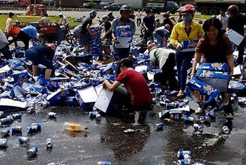 Hàng trăm người dân tham gia 'hôi của' khi xe bia lật. Ảnh chụp màn hình.