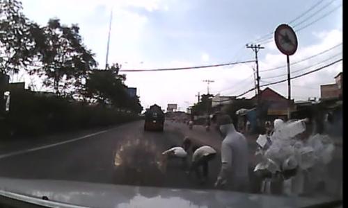 Hàng chục người hôi tiền nạn nhân đánh rơi trên đường. Ảnh chụp màn hình.