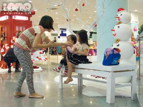 Hai em nhỏ được mẹ chụp hình lưu niệm ở một góc nhỏ trang trí Giáng sinh tại một trung tâm thương mại.