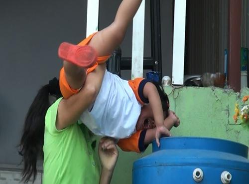 Bảo mẫu Thiên Lý và hành động dốc trẻ vào thùng nước. Ảnh chụp màn hình.