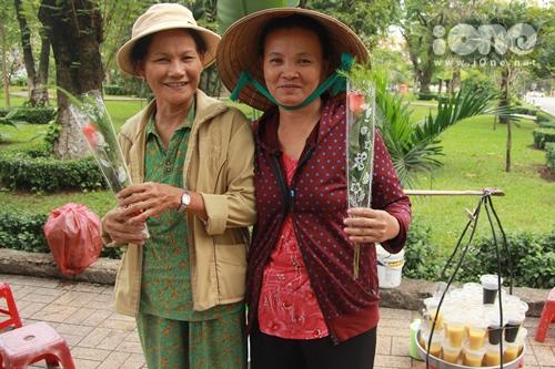 Hai cô bán chè ngọ cười vui vẻ trước những nhánh hoa hồng lần đầu tiên được tặng trong đời.