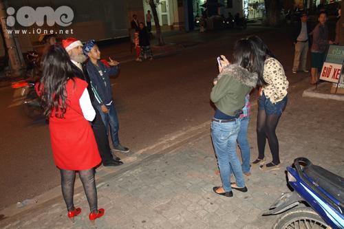 Một vị khách nước ngoài đội mũ ông già Noel đi lễ nhà thờ được các bạn trẻ xin chụp ảnh lưu niệm.