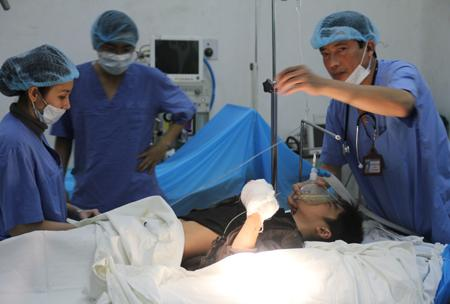 Dung đang được  các bác sĩ tiến hành phẫu thuật nối gân tay.