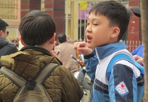 Vào giờ tan học tại cổng trường, một tốp học sinh lớp đang tranh giành nhau miếng sườn bò thơm cay, với các em thì đồ ăn này cay và rất ngon.