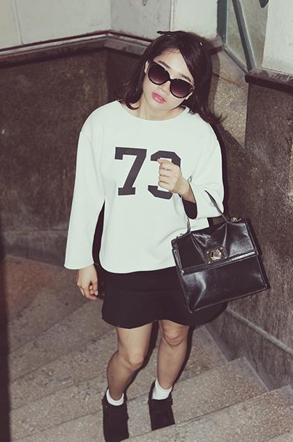 Cô chọn gam màu chủ đạo trắng đen với áo số, váy chữ A và cặp da truyền thống phối cùng ankle boot cho một chiều dạo phố mát mẻ.