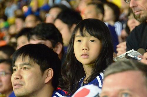 Cô bé Nhật chăm chú theo dõi đội nhà thi đấu.