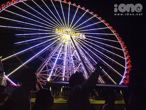 [Caption]Mở cửa từ cuối tuần qua, vòng đu quay Sun Wheel ở công viên châu Á  Đà Nẵng thu hút sự chú ý của đông đảo người dân, đặt biệt là các bạn trẻ đến tham quan, trải nghiệm như một điểm giải trí mới. Ánh điện từ 13 ngàn đèn Led trên đu quay tỏa ánh sáng dịu mắt, ấm ấp vào ban đêm.