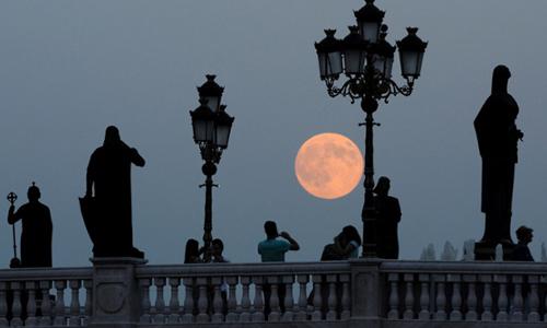 Nhiều người đứng ngắm siêu trăng trên cầu sông Vardar ở  Skopje, Macedonia.