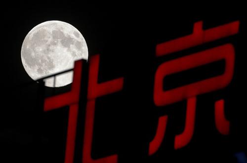 Siêu trăng sáng tỏ trên một bảng hiệu ở Bắc Kinh, Trung Quốc. Khi mặt trăng di chuyển sát đường chân trời, hiện tượng ảo giác sẽ khiến người quan sát cảm thấy nó lớn hơn so với kích thước thật.