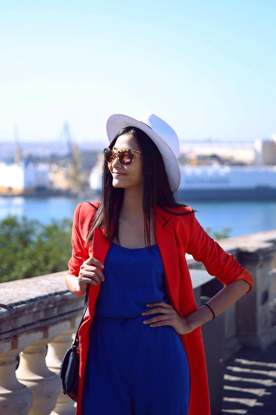 Trong bộ hình street style mới nhất trên hòn đảo Malta, Hoàng Thuỳ chọn cho mình bộ jumpsuit màu xanh đậm, khéo léo khi kết hợp màu sắc một cách hài hòa với chiếc áo blazer đỏ tươi. Đây cũng là phong cách thời trang được cô nàng định hình cho riêng mình trong thời gian này.