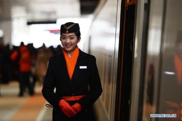 Nữ tiếp viên Li Jia đứng bên cạnh một toa tàu cao tốc tại khu vực nhà ga ở tỉnh Cam Túc, Trung Quốc.