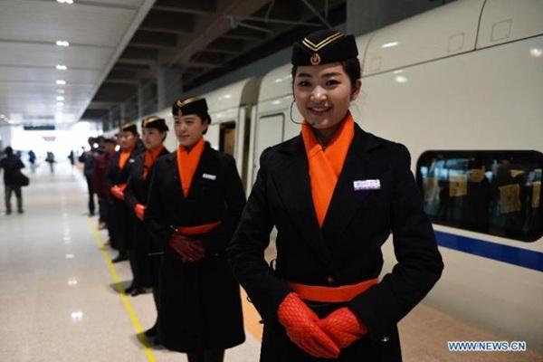 Các cô gái trong bộ đồng phục tiếp viên xinh đẹp được yêu cầu phải đứng đón khách trước cửa ra vào các toa tàu.