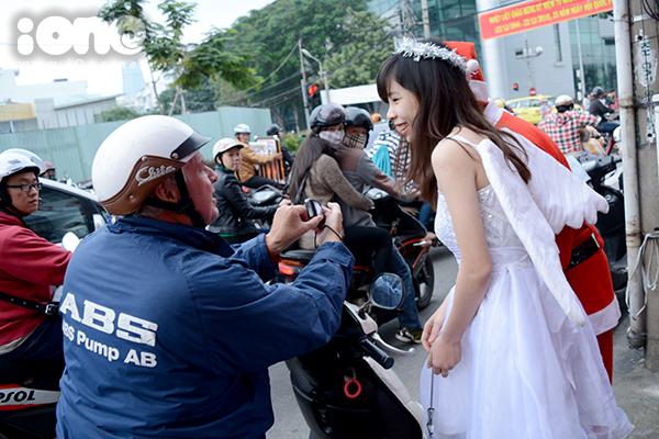 Một người nước ngoài dừng xe, chụp ảnh với thiên thần, ông già Noel.