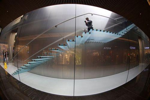Ở góc máy này, ta có thể thấy rõ kết cấu độc đáo của chiếc cầu thang. Toàn bộ đều được làm từ những tấm kính và cố định vào tường.