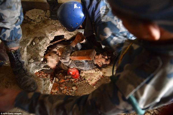 Một người đàn ông được kéo lên từ đống đổ nát ở Swyambhu, sát bên cạnh anh là thi thể   người bạn đã không may mắn sống sót. Cả hai bị gạch đá đè lên trong trận động đất.