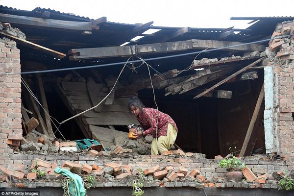 Cô gái trẻ nhặt nhạnh đồ dùng còn sót lại trong ngôi nhà bị hủy hoại.