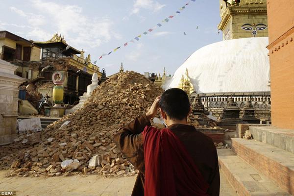 Một nhà sư đặt tay lên đầu, không thể tin được khi nhìn đền khỉ Syambhunaath Stupa, di   sản của đất nước Nepal, bị hủy hoại sau động đất. Nhiều đền thờ tại Nepal thu hút rất đông   du khách nay đã bị phá hủy.