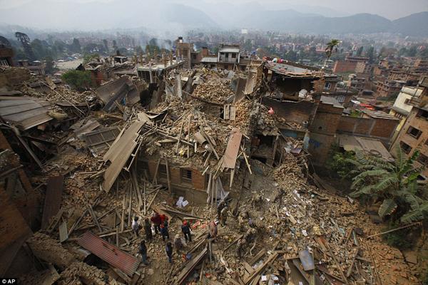 Đây là trận động đất mạnh nhất tại Nepal trong 81 năm qua. Số người chết hiện đã tăng lên   3.200 người, số người bị thương là hơn 6.500 người, nhiều công trình kiến trúc, đường sá   bị phá hủy. Trong hình, lực lượng cứu hộ đang tìm kiếm nạn nhân trong những đống đổ nát ở thành phố Bhaktapur.