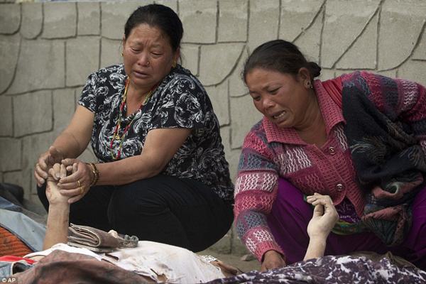 Hai người phụ nữ đau khổ nắm tay thân nhân đã qua đời đang nằm dưới những tấm vải   trắng mỏng. Rất nhiều thi thể nạn nhân được đặt trên đất thành hàng dài bên ngoài bệnh   viện. Những lễ hỏa táng tạm bợ đang được tiến hành ở nhiều nơi trên khắp Nepal.