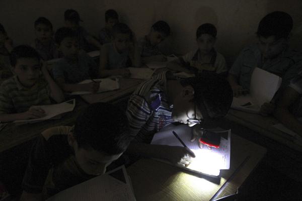 Ngày 5/6/2013, học sinh tại thành phố Aleppo ở Syria mò mẫm làm bài thi cuối kỳ trong   bóng tối do thiếu điện, một em học sinh đeo đèn pin trên trán. Ảnh: Muzaffar   Salaman/Reuters