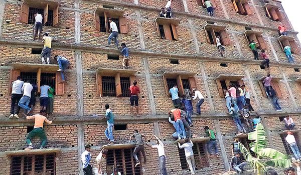 """Trong kỳ thi khối lớp 10 ở quận Vaishali, bang Bihar (Ấn Độ) tháng 3/2015, nhiều bậc phụ huynh đã bất chấp nguy hiểm, tay không leo 3-4 tầng lầu như Người Nhện để truyền """"phao"""" cho con em mình từ cửa sổ phòng thi. Gian lận, quay cóp phổ biến đến mức hầu hết người dân Ấn Độ đều coi nó là việc hiển nhiên và chính phủ thì bó tay."""