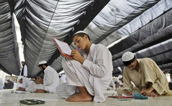 Các sinh viên Pakistan ngồi trên sàn nhà để làm bài thi hàng năm tại chủng viện Hồi giáo   Jamia Binoria ở Karachi, Pakistan vào ngày 8/6/2013. Ảnh: Fareed Khan/AP.