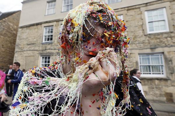 """Một sinh viên ĐH Oxford (Anh) bị ném """"rác"""" sau khi kết thúc kỳ thi ngày 7/6/2013. Đây là   một truyền thống của trường Oxford, các sinh viên sẽ bị bạn bè ném đủ thứ linh tinh vào   người khi thi xong. Ảnh: Stefan Wermuth/Reuters."""