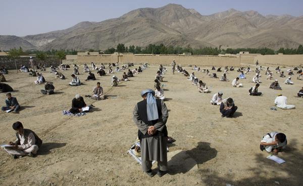 Học sinh một ngôi trường ở làng Sangarkhel (tỉnh Wardak, Afghanistan) ngổi thẳng hàng   theo đường kẻ sẵn trên nền sân đất để làm bài thi cuối kỳ, ngày 7/7/2009. Ảnh: Shamil   Zhumatov/Reuters.