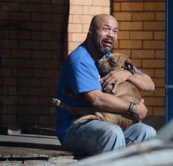 Người đàn ông đau đớn khôn xiết khi chó cưng mất vì hỏa hoạn. Ảnh: WorldTruth.TV.