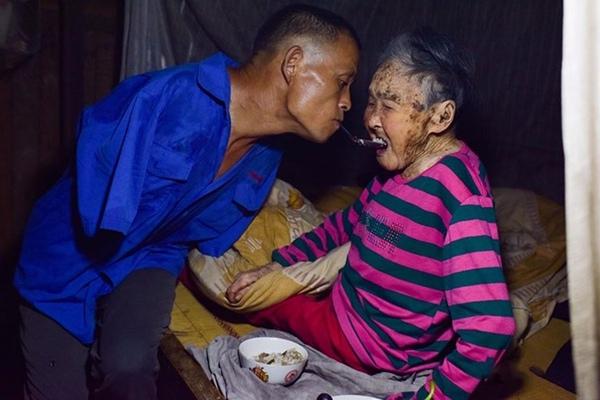 Bức ảnh người con bón cơm cho mẹ bằng miệng