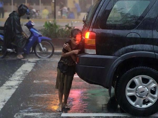 Bức ảnh cậu bé nép sau xe ô tô trong mưa gây xúc động. Ảnh: Oto Fun.