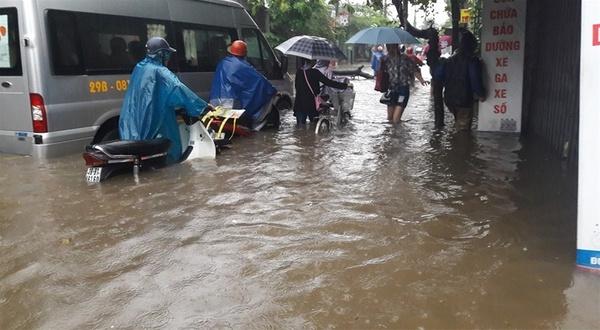 Ở nhiều khu vực, nước dâng cao ngập gần hết bánh xe, khiến người đi đường phải xuống xe hì hục dắt bộ.