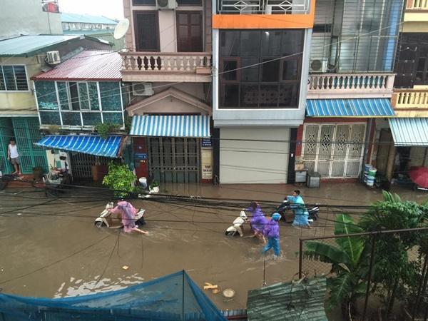 Một bạn chụp cảnh từ trên nhà cao nhìn xuống, thấy mọi người phải chật vật dắt xe vì nước ngập gần đến đầu gối.