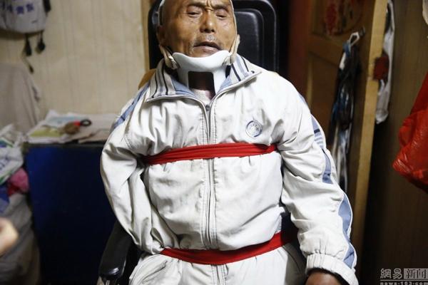 """Đông Đông buộc cố định cha vào xe lăn trước khi đi ăn xin. Ông luôn yêu cầu con   đưa mình cùng đi: """"Tôi không đi thì chẳng có ai tin cả""""."""