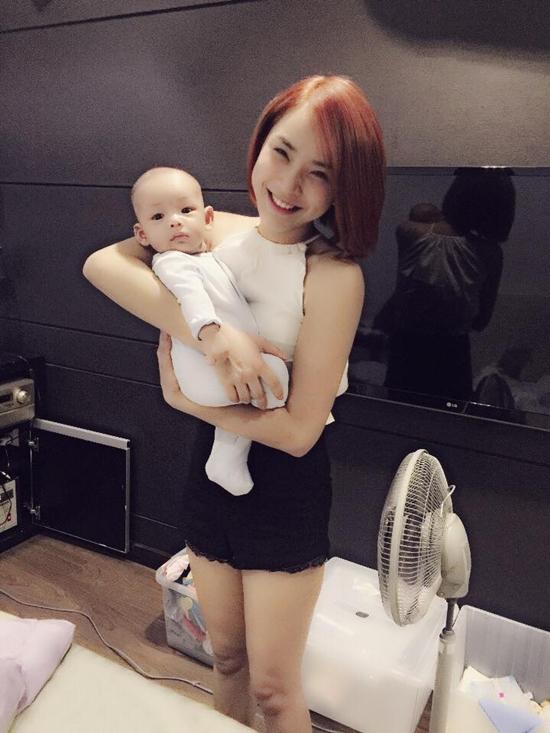 Hải Băng thích thú khi pose hình với một em bé.