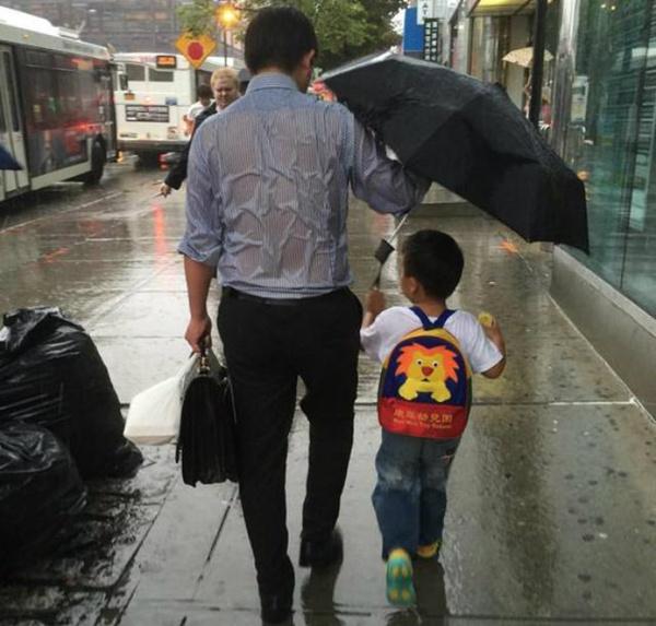 """Người bố che dù cho con trai và để mặc mình ướt mưa từng được bình chọn là """"ông bố quốc dân""""."""