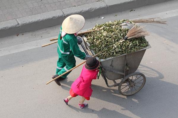 Cô bé chừng 5, 6 tuổi giúp mẹ đẩy rác chiều mùng 3 Tết. Ảnh: Hồ Hải Hoàng.