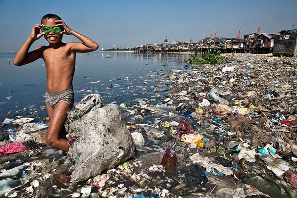 Cậu bé mưu sinh bằng cách lặn ngụp trong bãi rác bẩn thỉu mỗi ngày để nhặt nhạnh phế liệu tái chế. Ảnh: George Steinmetz.