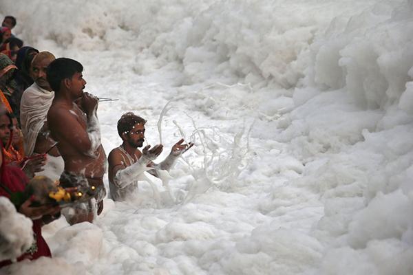 Nước thải công nghiệp và rác thải khiến dòng sông Yamuna ở New Delhi, Ấn Độ, bị ô nhiễm nặng nề sủi đầy bọt. Tuy nhiên, người dân địa phương vẫn tắm rửa và làm lễ cầu nguyện trên sông. Ảnh: businessinsider.in