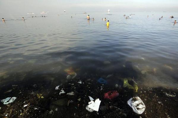 Nhiều người dân ra tắm ở vùng nước ô nhiễm trên vịnh Manila, dù họ đã được Bộ Môi trường và Tài nguyên Thiên nhiên Philippines cảnh báo rằng khu vực này không đủ điều kiện vệ sinh để tắm hay bơi lội. Ảnh: Ritchie B Tongo/EPA.