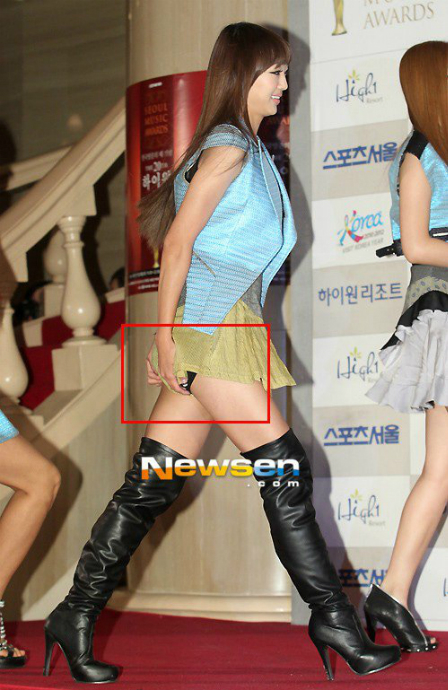 Váy quá ngắn và chất liệu mỏng khiến người đẹp showbiz Hàn luôn phải lấy tay che chắn vì sợ gió thổi.