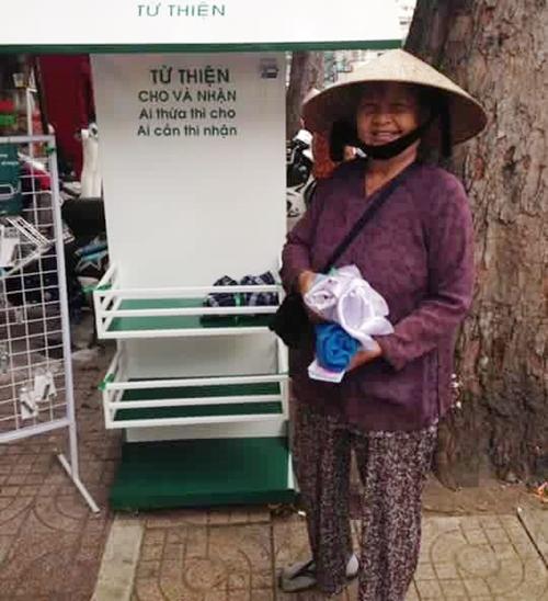 Một cô bán vé số vui vẻ nhận món quà từ sạp đồ từ thiện.