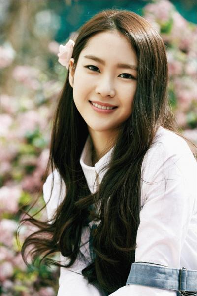 Ji Ho trông cực nữ tính, ngọt ngào với mái tóc thương hiệu của mình nhưng được uốn nhẹ, đánh rối phần đuôi tóc, kết hợp với một chiếc kẹp nơ kiểu hoa hồng đẹp mắt.