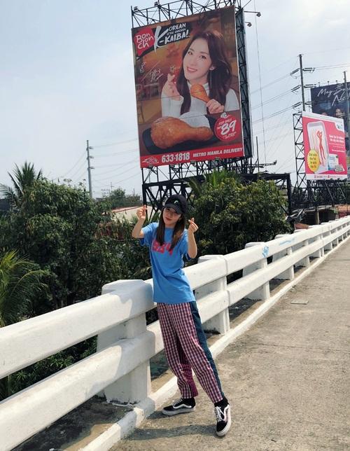 Dara mặc đồ thoải mái như đi chạy thể dục, nhí nhảnh pose hình bắn tim khi bắt gặp poster quảng cáo của chính mình trên đường.