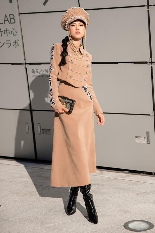 Ngày 2 dự sự kiện,  Hoàng Oanh rất ưa chuộng và theo đuổi phong cách monochrome với set đồ màu nâu nhạt của NTK Lý Giám Tiền khi tham dự ngày thứ 2 của Seoul Fashion Week. Bên cạnh đó cô cũng đã khéo léo lựa chọn clutch tối giản của Louis Vuitton như là 1 một item hợp trend. Màu sắc nhã nhặn tinh tế của chiếc clutch rất phù hợp với set đồ này của nữ MC. Bên cạnh đó, giày của Imis và chiếc mũ cầu kì của  Ngô Mạnh Đông Đông  người từng thiết kế nhiều chiếc mũ cho nhiều sao Việt như Hồng Nhung, Thanh Hằng... cũng tạo cho Hoàng Oanh một vẻ ngoài khác biệt và cực kì thời trang.