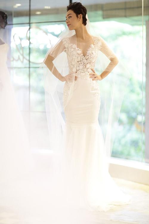 Chiếc váy có cổ chữ V được táp ren nửa kín, nửa hở giúp cô dâu trở nên gợi cảm mà không đánh mất sự duyên dáng. Điểm đặc sắc của bộ đầm chính là phần thân trên được làm từ nền vải voan trong suốt pha ren ngoại nhập, được đính kết với 3.000 viên pha lê cao cấp.